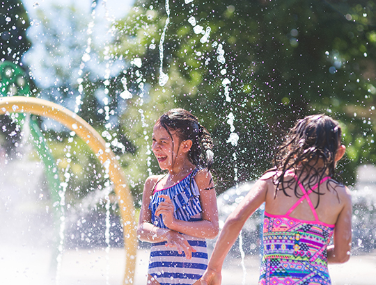 Girls frolic in the water play area at San Diego's Aquatica Waterpark