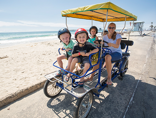 Family riding surrey bike on the beach path by the Bahia Resort Hotel in San Diego