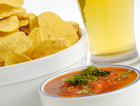 Close up of chips, salsa and a beer glass