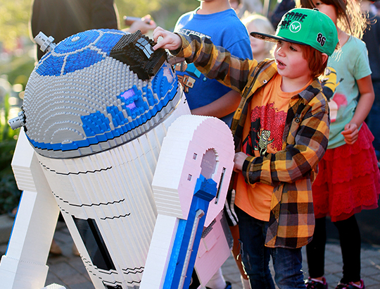 At LEGOLAND California, young boys and girls interact with a life-size Lego created R2-D2 star of Star Wars