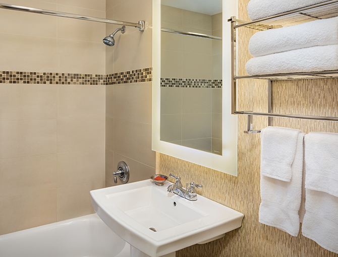 Bathroom view of sink, towel rack and bathroom with shower