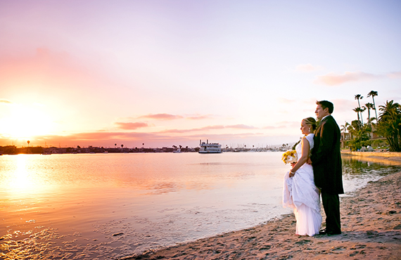 Wedding couple embracing on beach looking into the sunset
