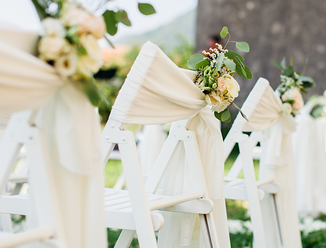 white chairs with ivory sashes and flowers