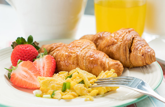 Eggs, croissant and fresh fruit on a plate
