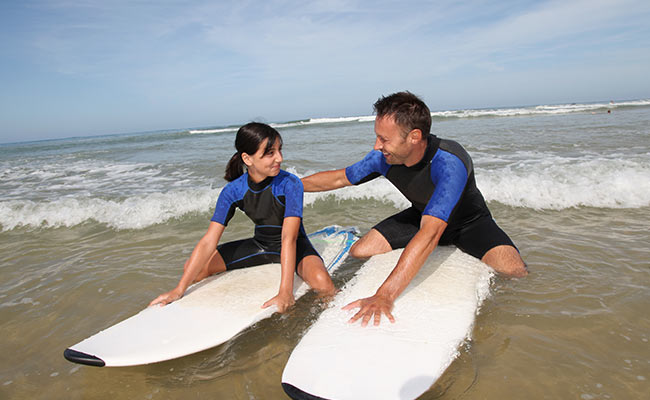 Summer bucket list: Man teaching young girl to surf