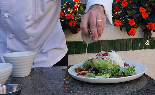Dressing being poured over the Avocado Salad