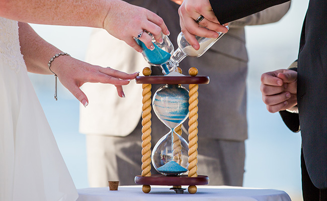 Bride and Groom pouring two different colors of sand into an hourglass vase at their Beach Wedding