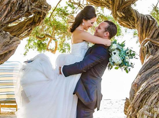 Bride and groom outdoors under trees arc