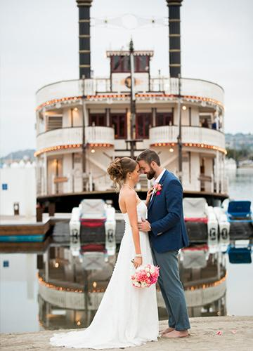 Wedding couple embracing in front of the William D. Evans on Mission Bay